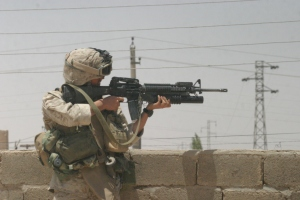 A grenadier with 3rd Platoon, K/3/2, fires on insurgents during Operation SPEAR in Karabilah, Iraq. June 17, 2005.