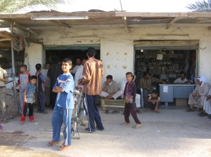 Iraqis next to shops used to conceal roadside bombs and weapons along Route Michigan, between Fallujah and Ramadi. September 17, 2006
