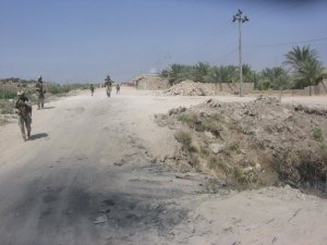 Marines with 3rd Battalion 2nd Marines patrol past the location where two Marines were killed by an IED just days before. Over the course of 2 weeks, six Marines and soldiers were killed within 200 yards of the mosque in the background. East Bidimnah, Iraq 2006