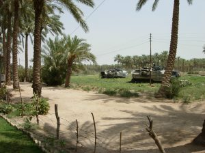 "Amphibious Assault Vehicles - better known as ""tracs"" or AAVs - cover avenues of approach while Marines clear the house of a high value target on Day 3 of Operation RUBICON. August 25, 2006"